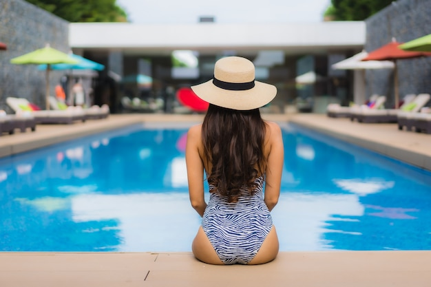 Beautiful portrait asian woman relax happy smile around outdoor swimming pool Free Photo