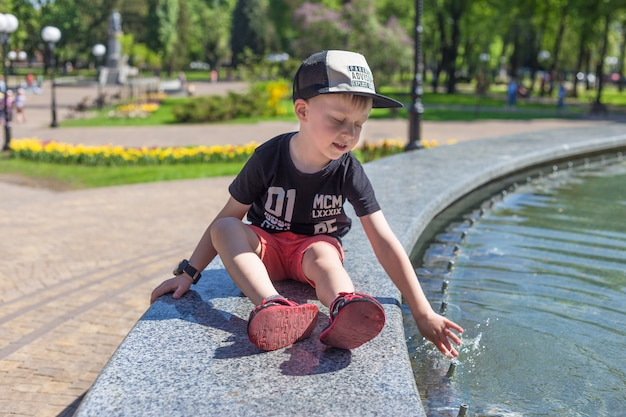 Beautiful portrait of a child near a fountain, in hot summer day Premium Photo