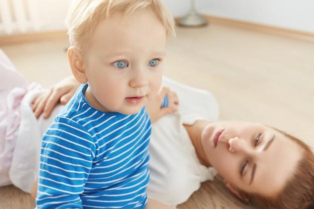 Bellissimo ritratto del ragazzino biondo con gli occhi azzurri e madre premurosa sdraiato sul pavimento a casa. piccolo bambino in vestiti blu che guarda avanti. la sua attraente mamma attenta che lo guarda con amore. Foto Gratuite