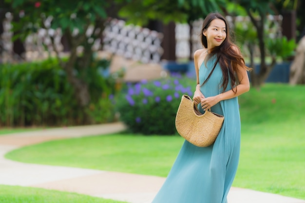Beautiful portrait young asian woman happy smile relax with walk in the garden Free Photo