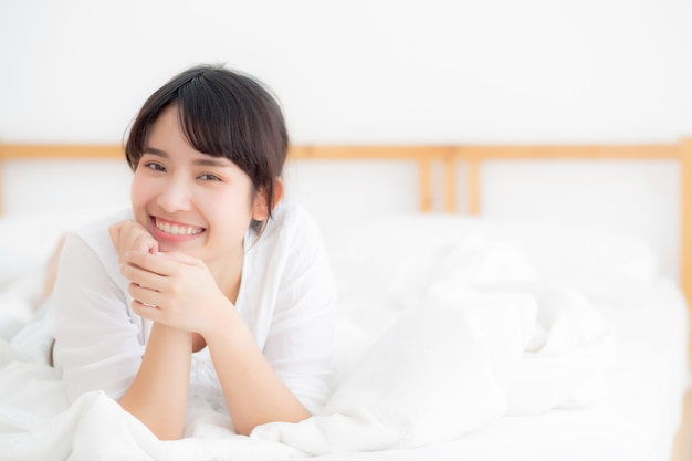 Beautiful portrait young asian woman lying and smile while wake up ...