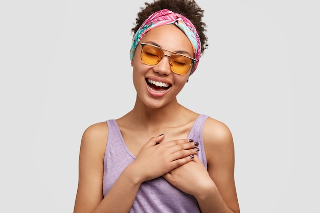Beautiful positive friendly looking female keeps both hands on chest, express gratitude to sister for help and advice, wears fashionale shades and sunglasses, isolated over white wall Free Photo