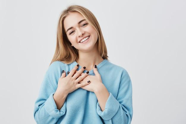 愛情と感謝に満ちた胸に手を差し伸べている彼女の心を示し、感謝と感謝の気持ちを込めて素敵な誠実な笑顔を持つ美しい肯定的なフレンドリーなヨーロッパの少女 無料写真