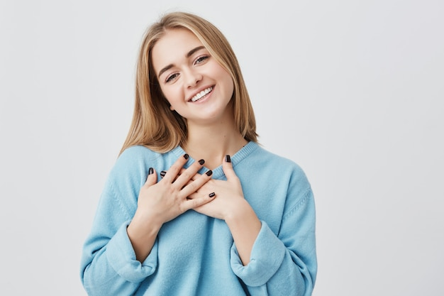 Beautiful positive friendly-looking young european girl with lovely sincere smile feeling thankful and grateful, showing her heart filled with love and gratitude holding hands on her breast Free Photo
