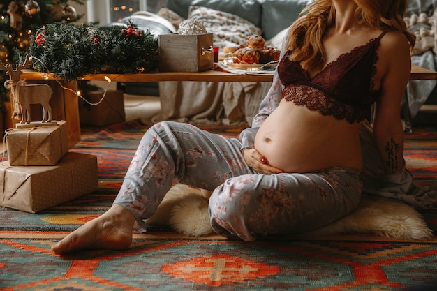Beautiful pregnant woman in comfy clothes sitting on a flor near the christmas tree. Premium Photo