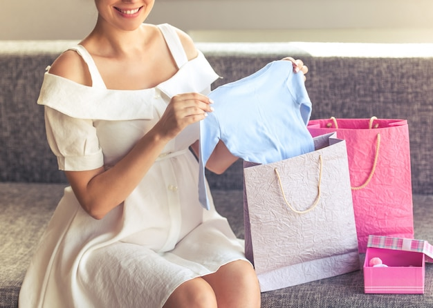Beautiful pregnant woman in dress holding cute baby clothes. Premium Photo