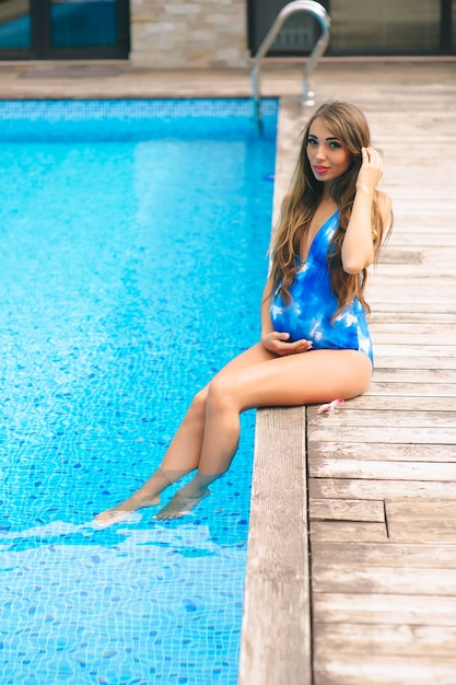 fa84bc2e7c09a Beautiful pregnant woman relaxing near the blue pool in a swimsuit Premium  Photo