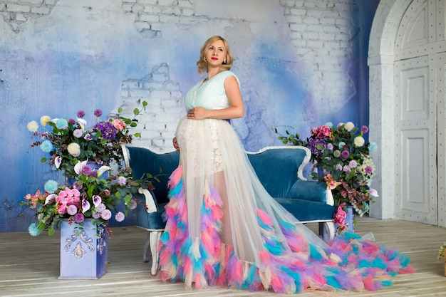 Premium Photo A Beautiful Pregnant Woman Stands With A Lush Floral Dress In A Loft Among Flowers On A Blue Wall