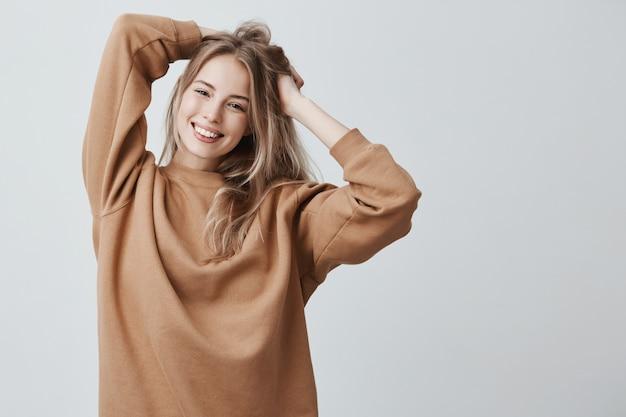 ルーズセーターを幸せそうに笑って、屋内で楽しんで、長いストレートの髪で遊んでかなり魅力的な若いブロンド美人。 無料写真