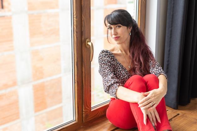 窓際に座っている美しいかなりスリムな女性。 Premium写真