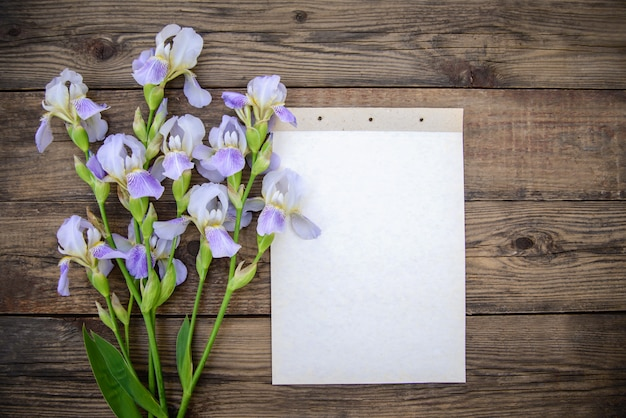 Beautiful purple flowers irises, a sheet of paper on a wooden background Premium Photo