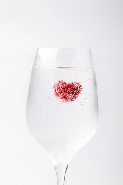 Beautiful raspberry in a water with bubbles in a wine glass. abstract Premium Photo