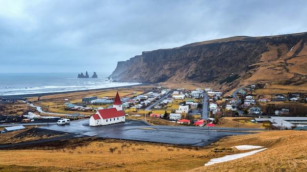 アイスランドの美しい赤い教会とヴィク村。 無料写真