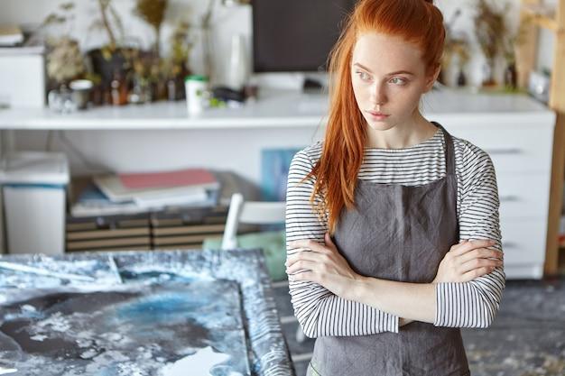 美しい赤髪の女性がエプロンを着て、手を組んで、しんみりと脇を見ながらワークショップに立ち、傑作を作った後しばらく休んでいます。創造的な生姜の若い女性 無料写真
