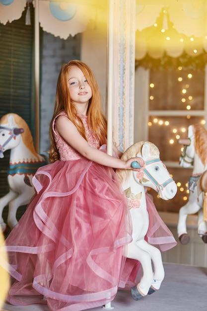 Beautiful red-haired girl long hair rides carousel Premium Photo