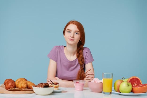 Una bella ragazza dai capelli rossi con i capelli intrecciati seduta a un tavolo, in procinto di fare colazione Foto Gratuite