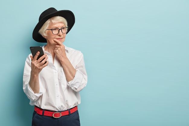 美しい赤い髪のしわのある女性は、あごを持って、思慮深く脇に見え、現代の携帯電話を持って、年金受給者のためのファッショナブルな服を着て、メッセージの内容について熟考しています。空白 無料写真