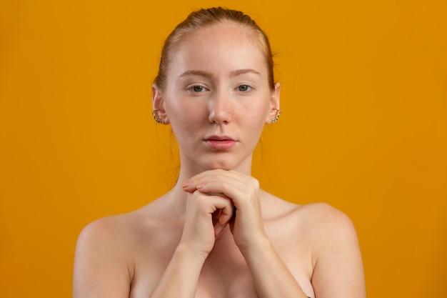 美しい赤毛の女性。保湿クリームまたはフェイスプライマー。若さとスキンケアのコンセプト。フェイシャルトリートメント。美容、美容、スキンケアのコンセプト。体液クリーム。 Premium写真