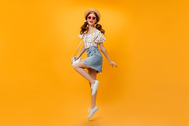Beautiful redhead woman in summer denim outfit and straw hat holding white bag and jumping on orange background. Free Photo