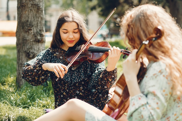 Beautiful and romantic girls in a park with a violin Free Photo