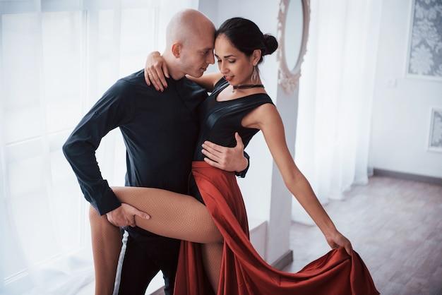 美しいロマンチックなポーズ。白い部屋でハゲ男と踊る赤と黒の服の若いきれいな女性 無料写真