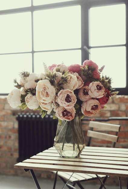 Beautiful roses bouquet on wooden table Free Photo