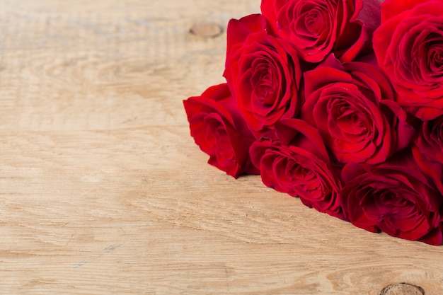 Beautiful roses on wooden table Free Photo
