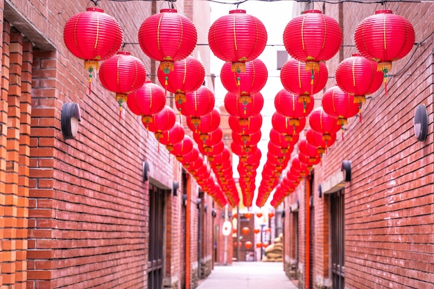 Beautiful round red lantern hanging on old traditional street, concept of chinese lunar new year festival, close up. the undering word means blessing. Premium Photo