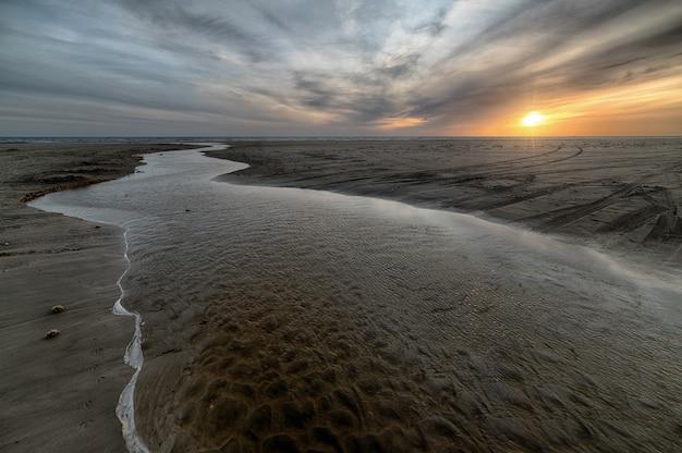 Bellissima spiaggia di sabbia con un mare durante la bassa marea Foto Gratuite