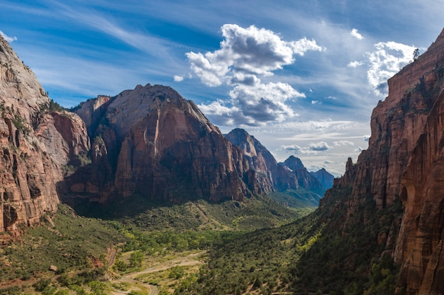 Beautiful scene of a green canyon surrounded by rocks under a bright summer sky Free Photo