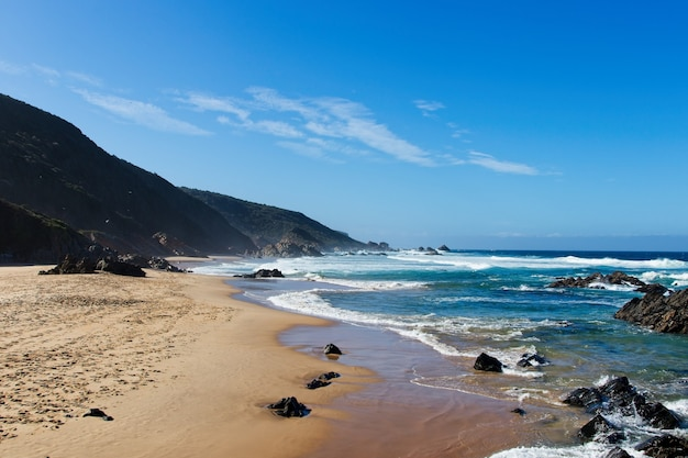 Beautiful scenery of a beach surrounded by hills under the clear sky Free Photo