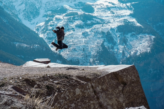 Beautiful scenery of a female jumping on top of a rocky mountain in suicide point in kalpa Free Photo