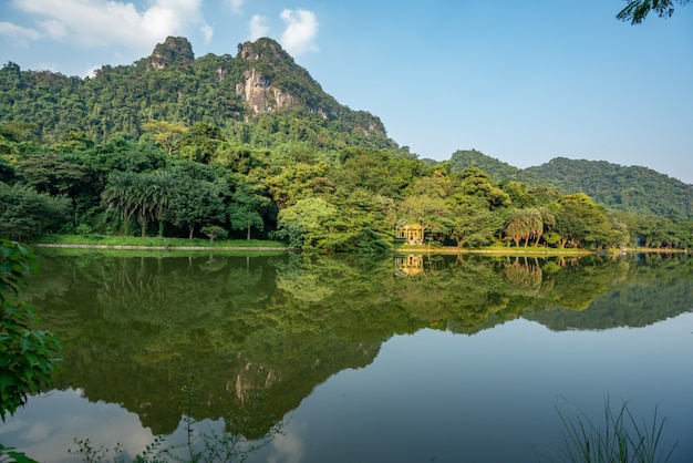 Beautiful scenery of green trees and high mountains reflected in the lake Free Photo