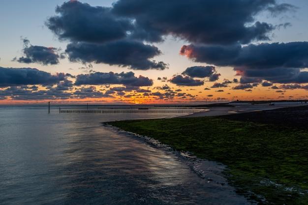 ゼーラント州ウエストカペレの穏やかな海に沈む美しい夕日の美しい風景 無料写真
