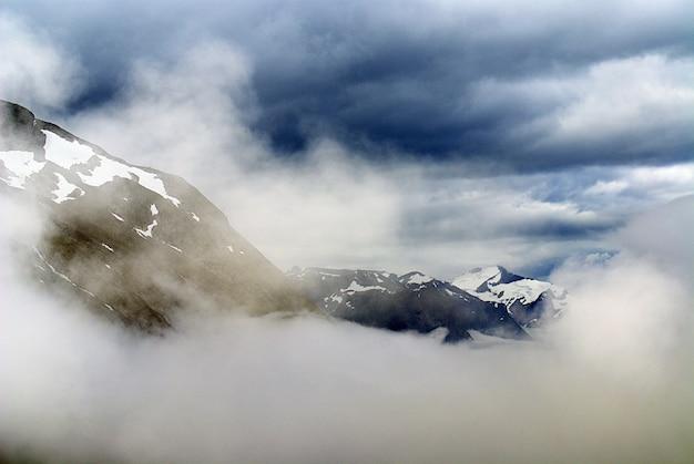 Красивые пейзажи горного хребта, покрытого снегом под белыми облаками в норвегии Бесплатные Фотографии