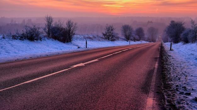 日の出の雪に覆われた木々に囲まれた道路の美しい風景 無料写真