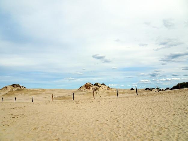 ポーランド、レーバの曇り空の下で砂浜の美しい風景 無料写真