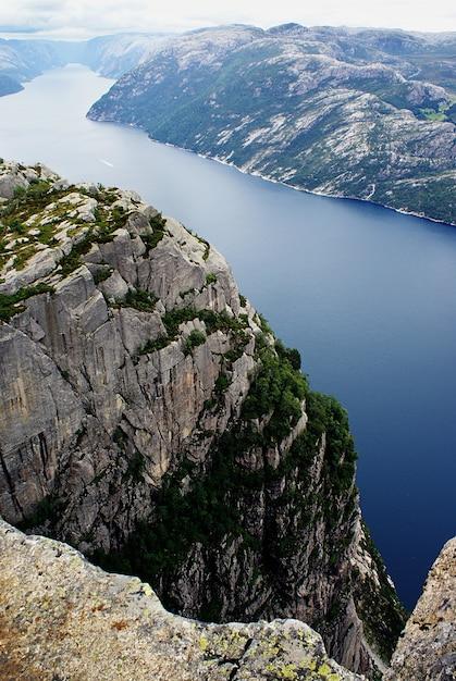 ノルウェー、スタヴァンゲルの曇り空の下の湖の近くの有名なプレーケストーレンの崖の美しい風景 無料写真