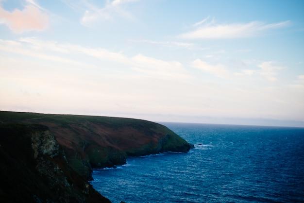 Красивые пейзажи скальных образований у моря в дневное время Бесплатные Фотографии