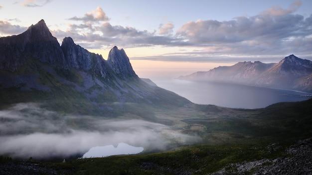 夕焼けの息を呑むような曇り空の下、海沿いの岩の崖の美しい風景 無料写真