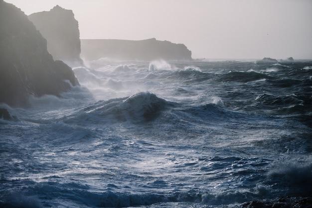 바위 위에 부서지는 파도의 아름다운 풍경 무료 사진