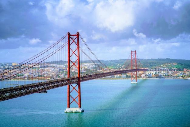 息をのむような雲の形成の下でポルトガルの25 de abril橋の美しい風景 無料写真