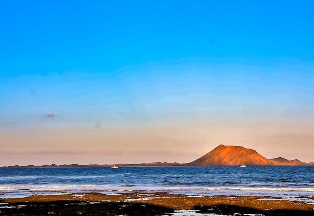日没時に丘に囲まれた海の美しい風景 無料写真