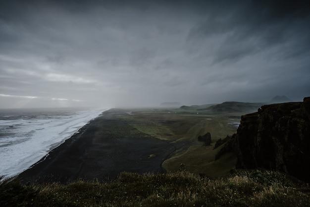 アイスランドの霧に包まれた岩層に囲まれた海の美しい風景 無料写真
