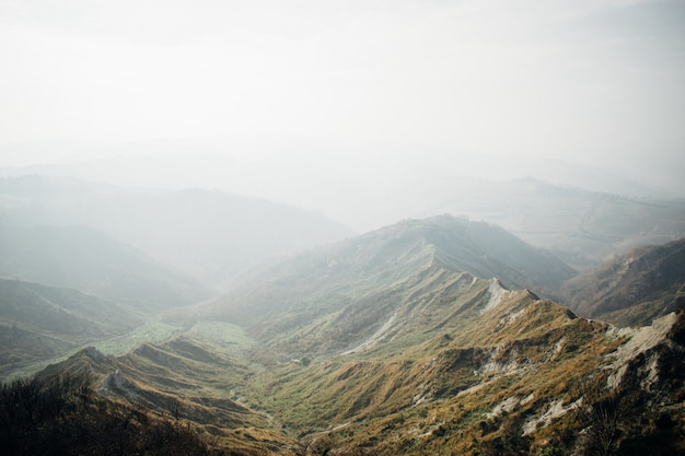 Beautiful scenery of a range of green mountains enveloped in fog Free Photo