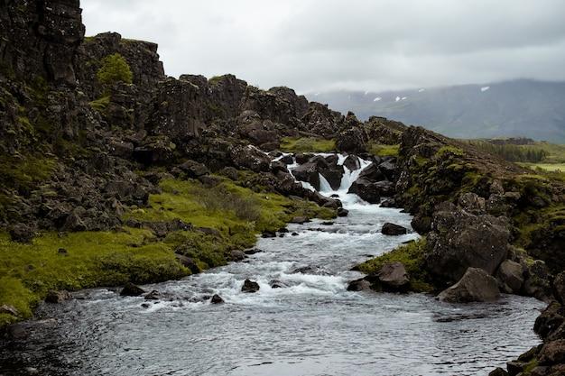Splendido scenario di un fiume che scorre vicino a formazioni rocciose in islanda Foto Gratuite