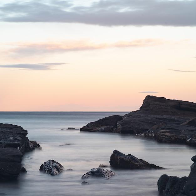 Splendido scenario di formazioni rocciose nel mare sotto il cielo colorato mozzafiato Foto Gratuite