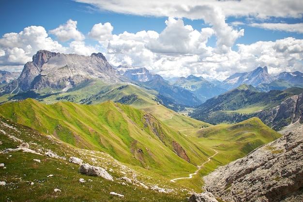 Splendido scenario di montagne rocciose con un paesaggio verde sotto un cielo nuvoloso Foto Gratuite