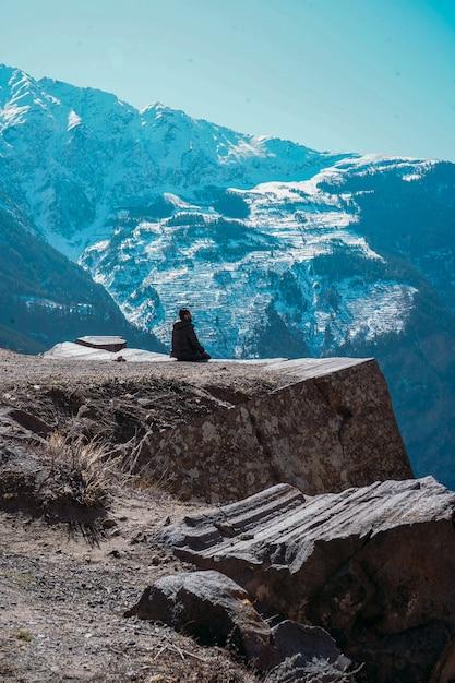 Красивый пейзаж с одиноким человеком, смотрящим на заснеженные горы в самоубийственной точке в кальпе Бесплатные Фотографии
