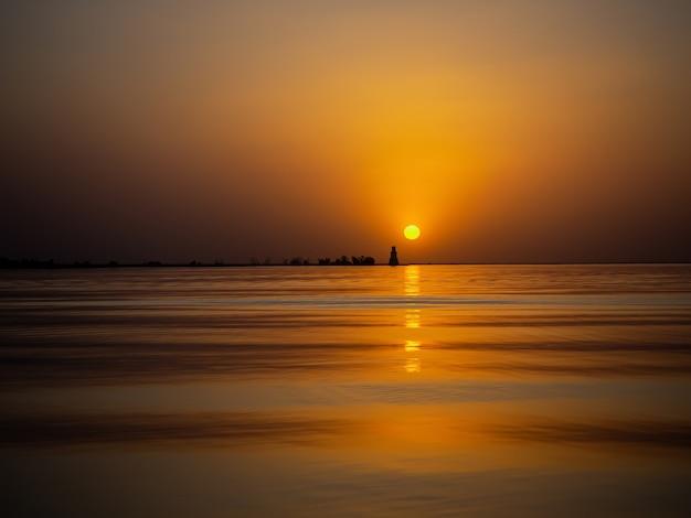 Красивый живописный пейзаж. золотой закат на море. Premium Фотографии